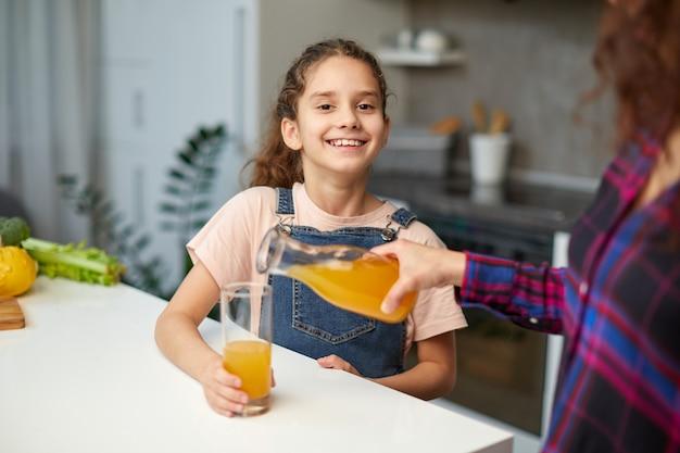Porträt einer mutter schenkt ihrer süßen tochter orangensaft zum frühstück ein