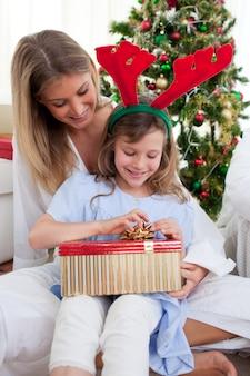 Porträt einer mutter und ihrer tochter, die weihnachtsgeschenke auspacken