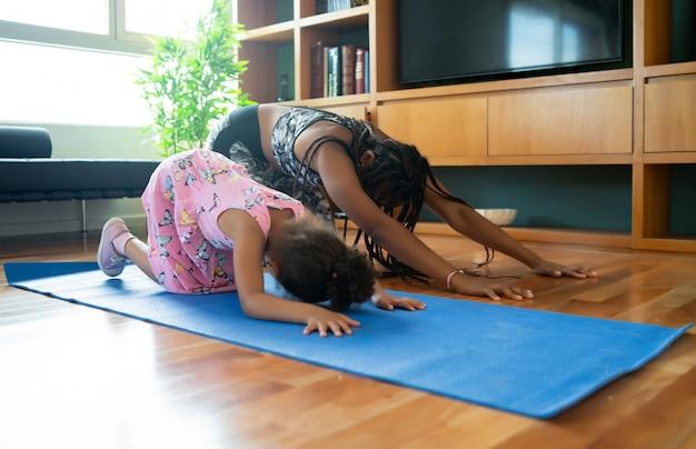 Porträt einer mutter und tochter, die yoga-übungen machen, während sie zu hause bleiben. sportkonzept