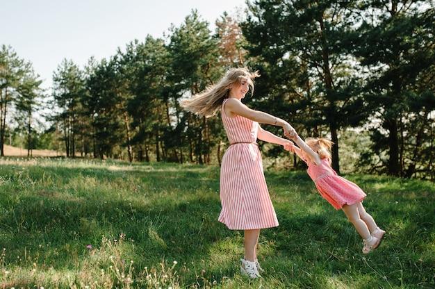 Porträt einer mutter wirft und dreht die tochter im sommerurlaub auf den händen in der natur. mutter und mädchen, die bei sonnenuntergang im park spielen. konzept der freundlichen familie. nahaufnahme.