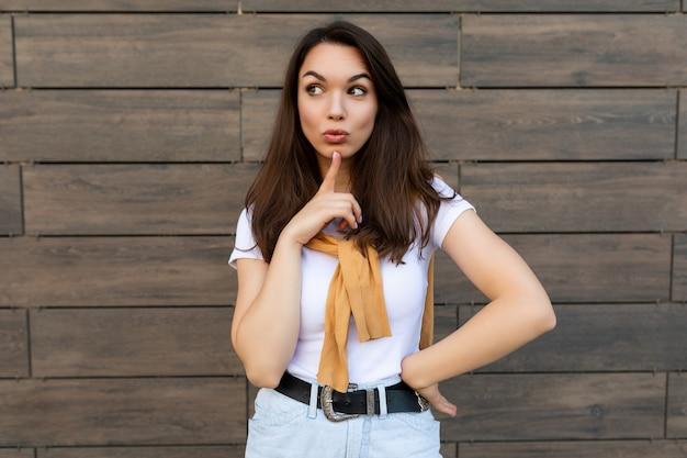 Porträt einer nachdenklich träumenden jungen brunet-frau, die ein lässiges weißes t-shirt mit gelbem pullover trägt, der in der nähe der braunen wand auf der straße steht?