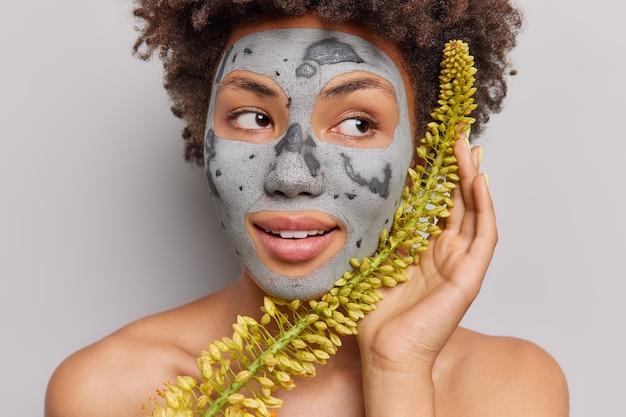 Porträt einer nachdenklichen afroamerikanischen frau trägt eine pflegende kräuter-ton-maske auf, die pflanze hält