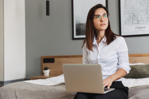 Porträt einer nachdenklichen erwachsenen geschäftsfrau im formellen anzug, die auf dem laptop tippt, während sie auf dem bett in der wohnung sitzt