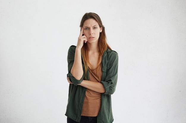 Porträt einer nachdenklichen frau mit europäischem aussehen, die schaut, während sie verwirrt die augenbrauen runzelt und den finger an der schläfe hält, um sich zu konzentrieren und eine geeignete lösung zu finden