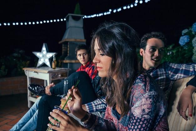 Porträt einer nachdenklichen jungen frau, die cocktail mit ihren freunden in einer party im freien hält. konzept für freundschaft und feiern.