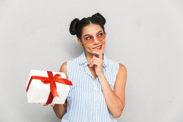 Porträt einer nachdenklichen jungen frau in der sonnenbrille lokalisiert, geschenkbox haltend