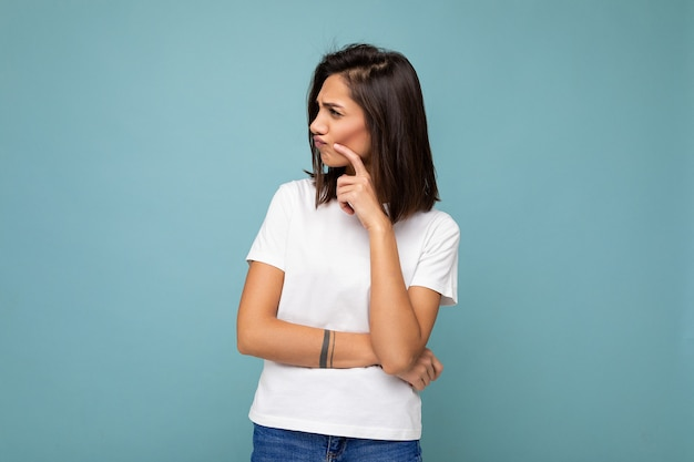 Porträt einer nachdenklichen jungen, hübschen, hübschen, brünetten frau mit aufrichtigen emotionen, die ein lässiges weißes t-shirt für das modell trägt, einzeln auf blauem hintergrund mit kopienraum.