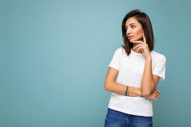 Porträt einer nachdenklichen jungen, schönen brünetten frau mit aufrichtigen emotionen, die ein lässiges weißes t-shirt für das modell trägt, isoliert über blauem hintergrund mit kopienraum und denken.