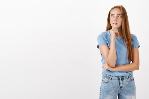 Porträt einer nachdenklichen, konzentrierten, niedlichen und weiblichen frau mit langen roten haaren und sommersprossen, die sich mit der faust nach links blinzelnd stützt und dabei denkt, eine entscheidung zu treffen oder zweifelhaft zu sein
