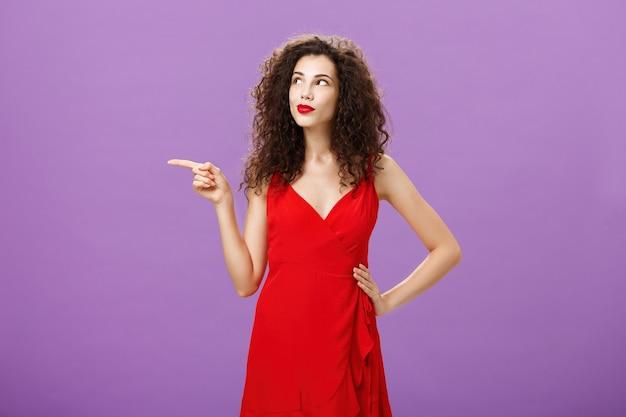 Porträt einer nachdenklichen und verträumten charmanten frau mit lockiger frisur im eleganten roten abendkleid...
