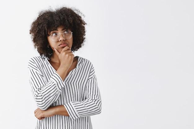 Porträt einer nachdenklichen verträumten und konzentrierten niedlichen dunkelhäutigen frau mit lockigem haar, das schmollt, die hand am kinn hält und auf die obere rechte ecke schaut, während sie nachdenkt und sich eine idee oder einen plan ausdenkt