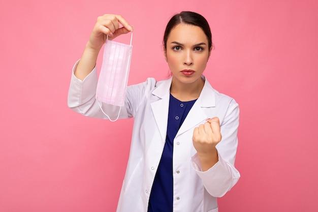 Porträt einer negativen attraktiven jungen ärztin im weißen kittel, die eine medizinische maske hält