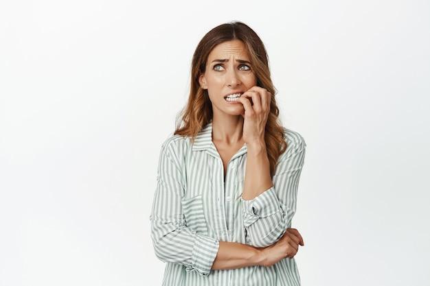 Porträt einer nervösen brünetten frau, die finger beißt und besorgt beiseite schaut