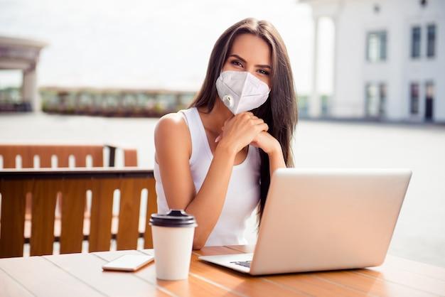 Porträt einer netten, attraktiven, gesunden dame, die eine wiederverwendbare sicherheits-atemschutzmaske n95 trägt