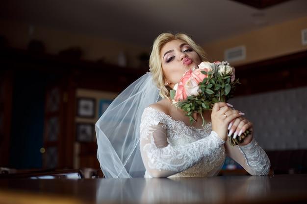 Porträt einer netten braut mit einem blumenstrauß von rosen innen. junge glücklich lächelnde braut hält blumenstrauß.