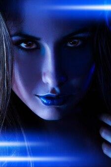 Porträt einer netten frau mit blauen leuchtenden linien im studio