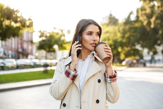 Porträt einer netten frau mit mantel, die kaffee zum mitnehmen trinkt und beim gehen auf der stadtstraße auf dem handy spricht