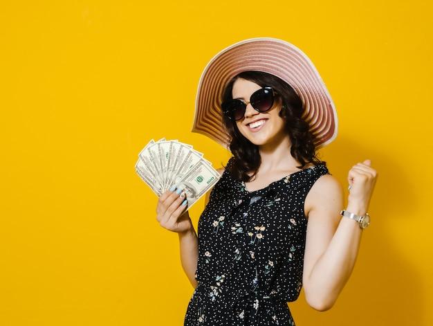 Porträt einer netten jungen frau mit der sonnenbrille und hut, die geldbanknoten halten und über gelber wand lokalisiert feiern