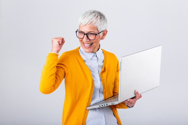 Porträt einer netten reifen frau mit einer laptop-computer und feiern des erfolgs lokalisiert über grauem hintergrund.