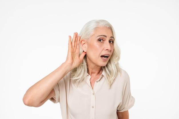 Porträt einer neugierigen reifen frau, die versucht, etwas zu hören