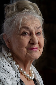 Porträt einer neunzigjährigen frau. schöne alte dame. luxuriöse großmutter auf einem schwarzen hintergrund. ältere schönheit. der grauhaarige, gepflegte rentner.