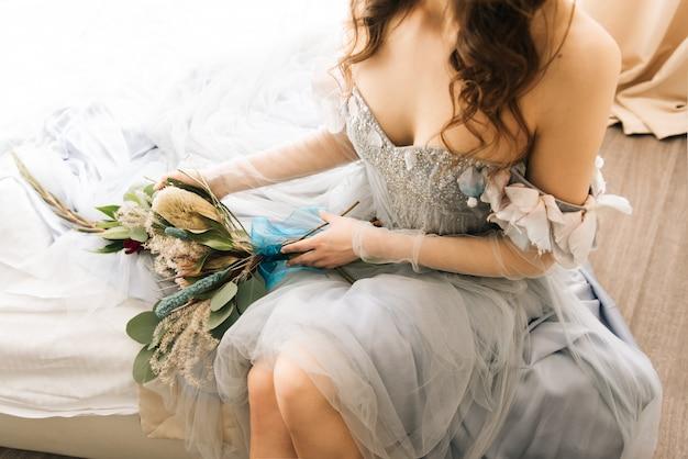 Porträt einer niedlichen braut in einem hochzeitskleid mit einem strauß exotischer blumen-protea. hochzeitsmorgen