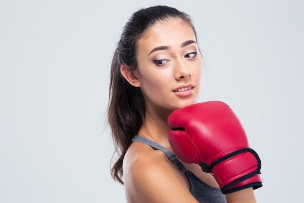 Porträt einer niedlichen fitnessfrau mit den boxhandschuhen, die lokal auf einer weißen wand stehen