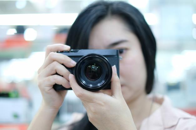 Porträt einer niedlichen frau ein bild mit einer digitalkamera am unscharfen hintergrund