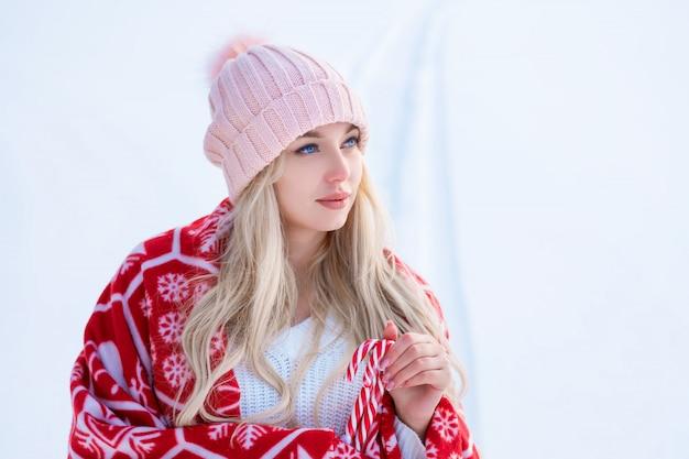 Porträt einer niedlichen frau gegen den schnee in einem rosa hut und einem roten plaid, das für die kamera aufwirft