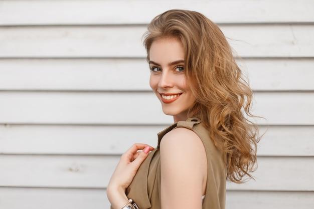 Porträt einer niedlichen glücklichen jungen frau mit einem schönen lächeln mit natürlichem make-up mit lockigem blondem haar mit blauen augen in sommerkleidung, die nahe einer weißen holzwand aufwirft. fröhliches positives mädchen