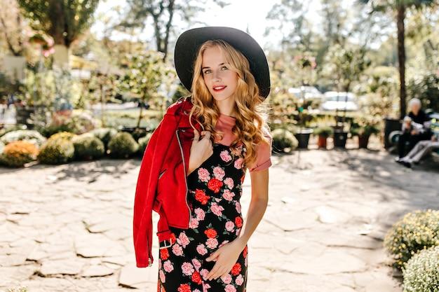 Porträt einer niedlichen grünäugigen frau mit welligem blindem haar, gekleidet in rote lederjacke und kleid mit rosen.