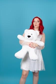 Porträt einer niedlichen weiblichen frau, die einen großen weißen teddybär umarmt und einen kuss bläst