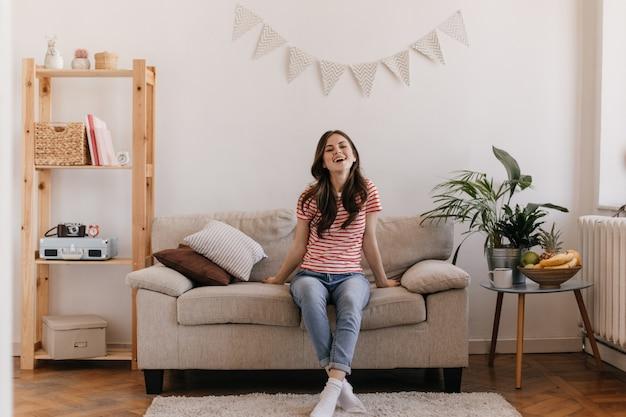 Porträt einer optimistischen frau in gestreiftem oberteil und jeanshose