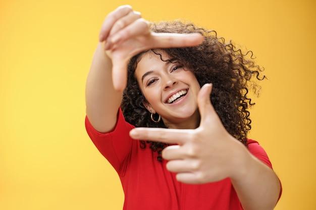 Porträt einer optimistischen, glücklichen und kreativen studentin, die ihre neue wohnung als verlängerte hände vorstellt und rahmengesten zeigt, die durch sie amüsiert und sorglos über gelber wand lächeln.