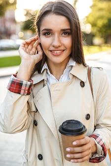 Porträt einer optimistischen, süßen frau mit mantel, die kaffee zum mitnehmen trinkt und beim gehen auf der stadtstraße lächelt