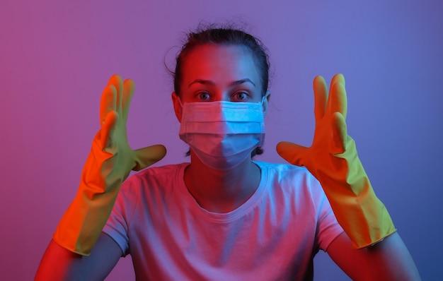 Porträt einer panikfrau in einer medizinischen maske und handschuhen. rosa blaues neonlicht mit farbverlauf. pandemieschutz covid-19