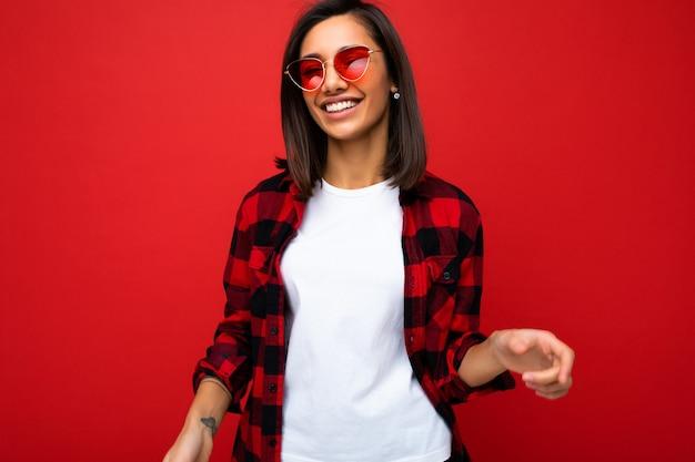 Porträt einer positiv fröhlich lächelnden jungen brünetten frau im lässigen weißen t-shirt für modell, stilvolles rotes karohemd und trendige rote sonnenbrille einzeln auf rotem hintergrund mit kopienraum.
