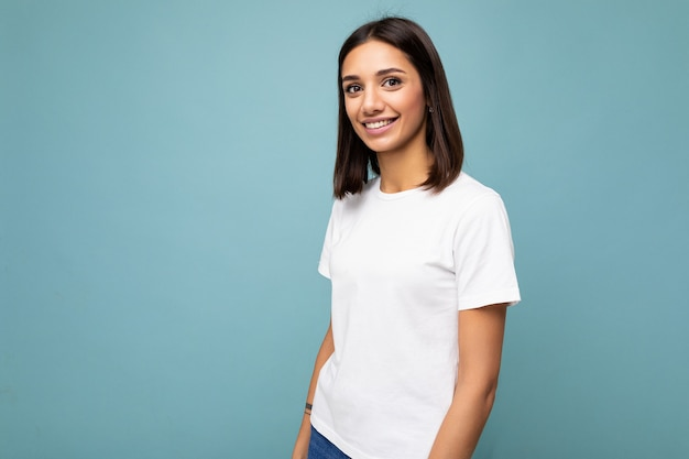 Porträt einer positiv fröhlichen modischen lächelnden jungen brünetten frau im lässigen weißen t-shirt für das modell einzeln auf blauem hintergrund mit kopienraum