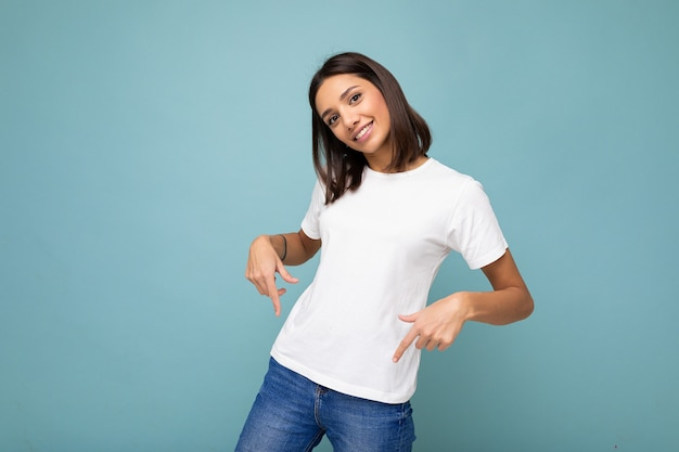 Porträt einer positiv glücklich lächelnden jungen schönen brünette mit aufrichtigen emotionen, die ein lässiges weißes t-shirt für das modell trägt, einzeln auf blauem hintergrund mit kopienraum und auf leeren raum zeigend