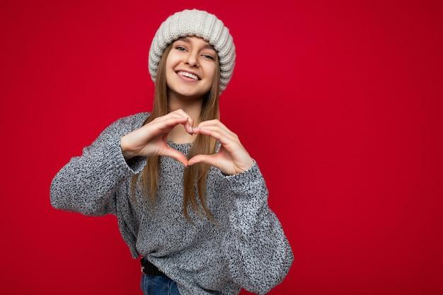 Porträt einer positiv lächelnden jungen netten süßen dunkelblonden frau mit aufrichtigen emotionen, die grau trägt