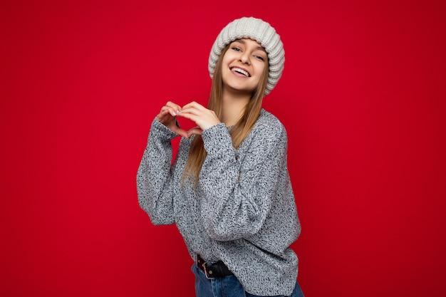 Porträt einer positiv lächelnden jungen schönen dunkelblonden frau mit aufrichtigen emotionen, die grau trägt