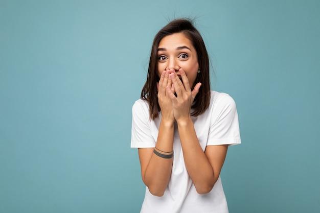 Porträt einer positiv überraschten jungen schönen brünetten frau mit aufrichtigen emotionen, die ein lässiges weißes t-shirt für das modell trägt, isoliert auf blauem hintergrund mit kopienraum und den mund mit den händen bedeckend