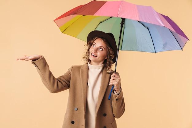Porträt einer positiven emotionalen glücklichen frau im hut lokalisiert auf der beige wand, die regenschirm hält.