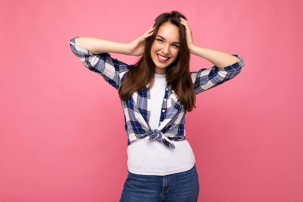 Porträt einer positiven, fröhlichen, modischen frau im hipster-outfit, isoliert auf rosa