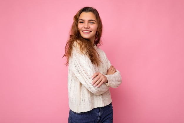 Porträt einer positiven, fröhlichen, modischen frau in formeller kleidung, die die kamera einzeln auf rosa betrachtet