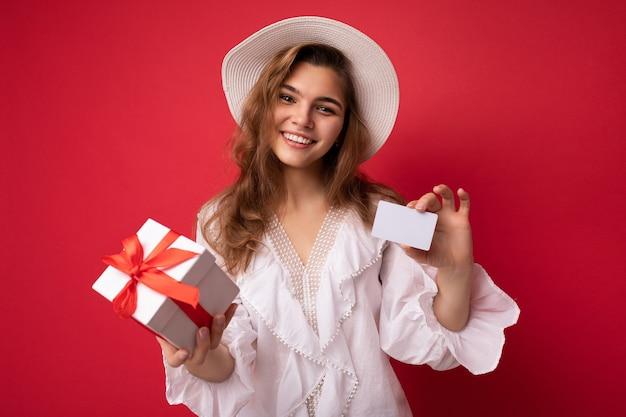 Porträt einer positiven, fröhlichen, modischen frau in formeller kleidung, die geschenkbox und kreditkarte hält