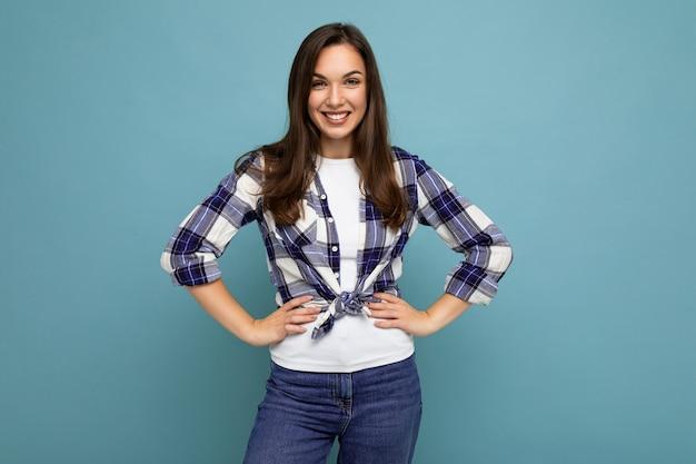 Porträt einer positiven fröhlichen modischen frau in hipster-outfit auf blauem hintergrund mit