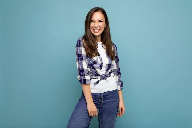 Porträt einer positiven, fröhlichen, modischen frau in hipster-outfit isoliert auf blauem hintergrund mit kopierraum