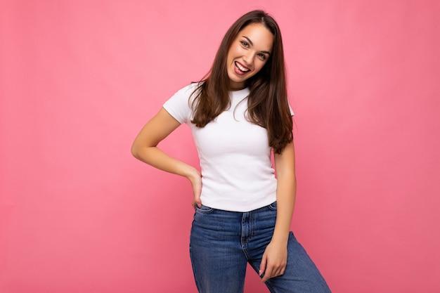 Porträt einer positiven fröhlichen modischen frau in lässigem t-shirt für mock-up einzeln auf rosa