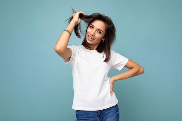 Porträt einer positiven, fröhlichen, modischen lächelnden jungen brunettefrau im lässigen weißen t-shirt für das modell einzeln auf blauem hintergrund mit kopienraum.